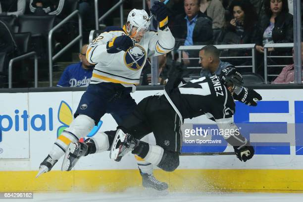 Los Angeles Kings Defenceman Alec Martinez gets checked hard onto the ice by Buffalo Sabres Left Wing Marcus Foligno in the game between the Buffalo...
