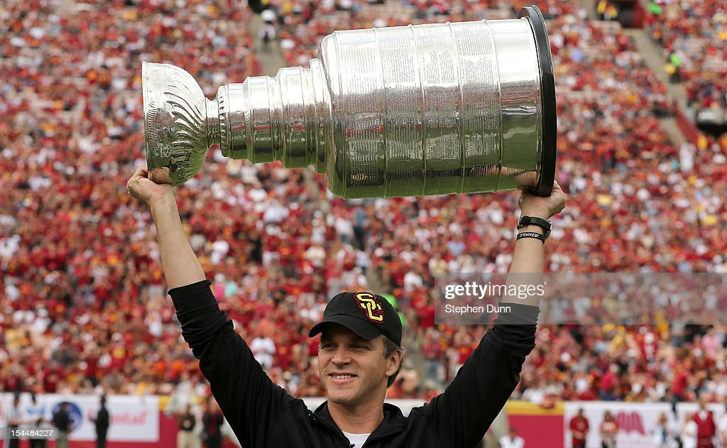 Los Angeles Kings executive Luc Robitaille and Hall of Fame hockey player holds up the Stanley Cup during a ceremony during the game between the USC Trojans and the Colorado Buffaloes at the Los Angeles Memorial Coliseum on October 20,2012 in Los Angeles, California. USC won 50-6.