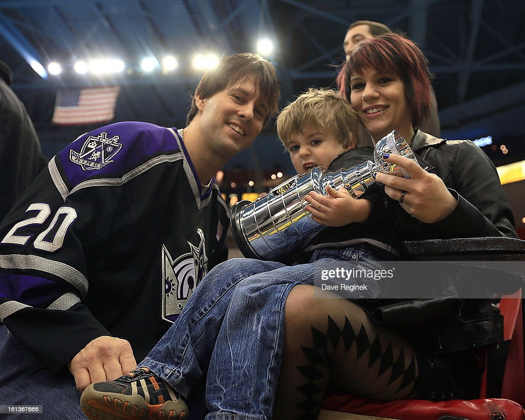 Los Angeles Kings fans pose for a photo with their mini Stanley Cup before a NHL game against the Detroit Red Wings at Joe Louis Arena on February 10, 2013 in Detroit, Michigan.