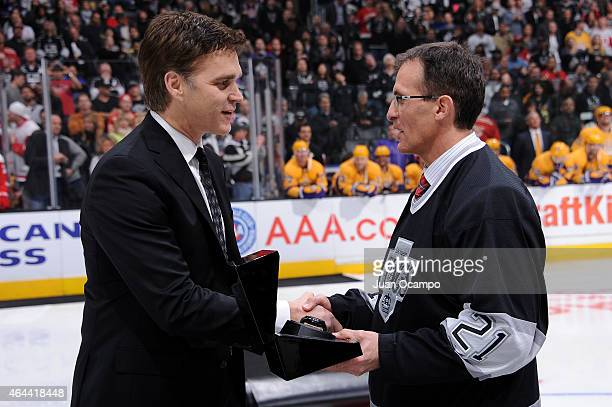 Los Angeles Kings President of Business Operations Luc Robitaille presents Tony Granato with a Graham time piece during a presentation as part of...