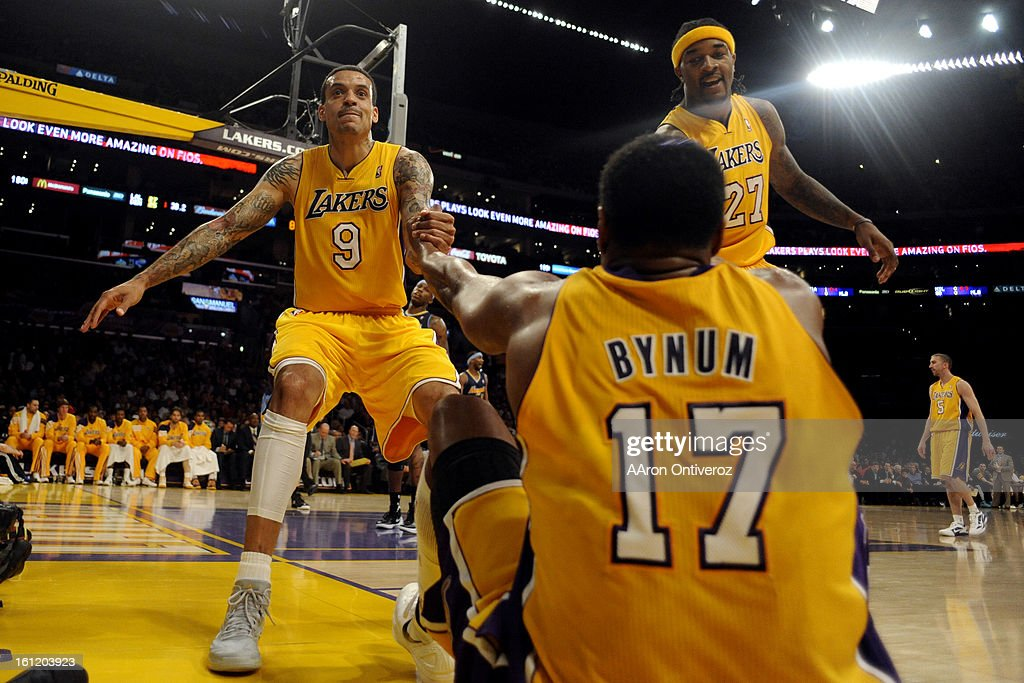Los Angeles Lakers center Andrew Bynum is helped up by small forward Matt Barnes and center Jordan Hill during the first half of game two of their...