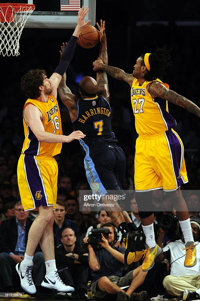 Los Angeles Lakers center Jordan Hill and power forward Pau Gasol defend Denver Nuggets power forward Al Harrington during the first half of game...