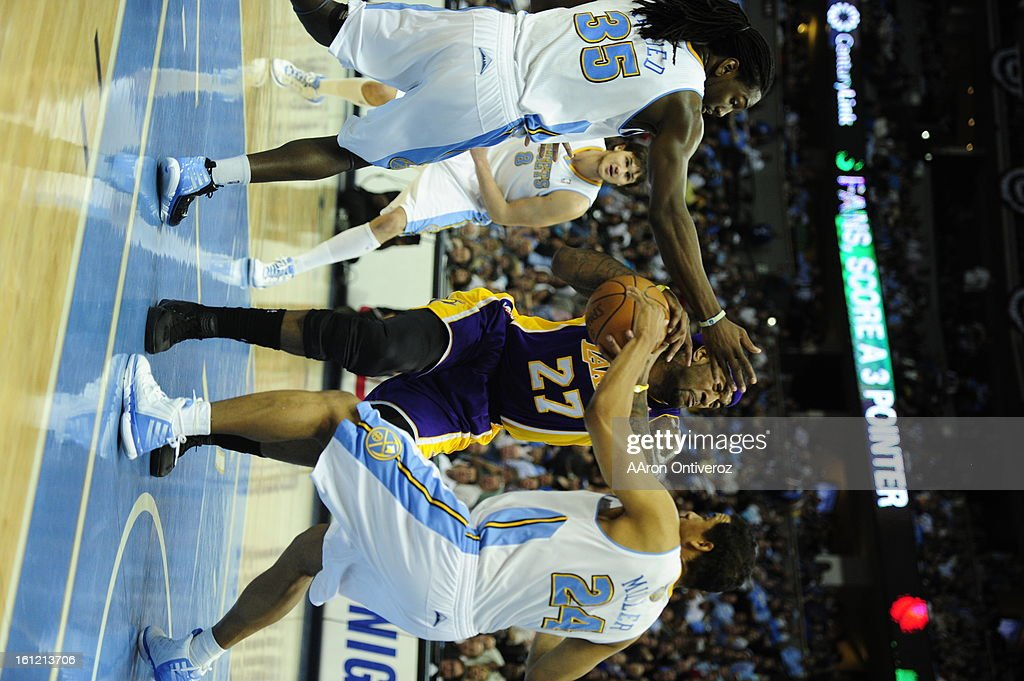 Los Angeles Lakers center Jordan Hill gets sandwiched by Denver Nuggets point guard Andre Miller and Denver Nuggets forward Kenneth Faried during the...