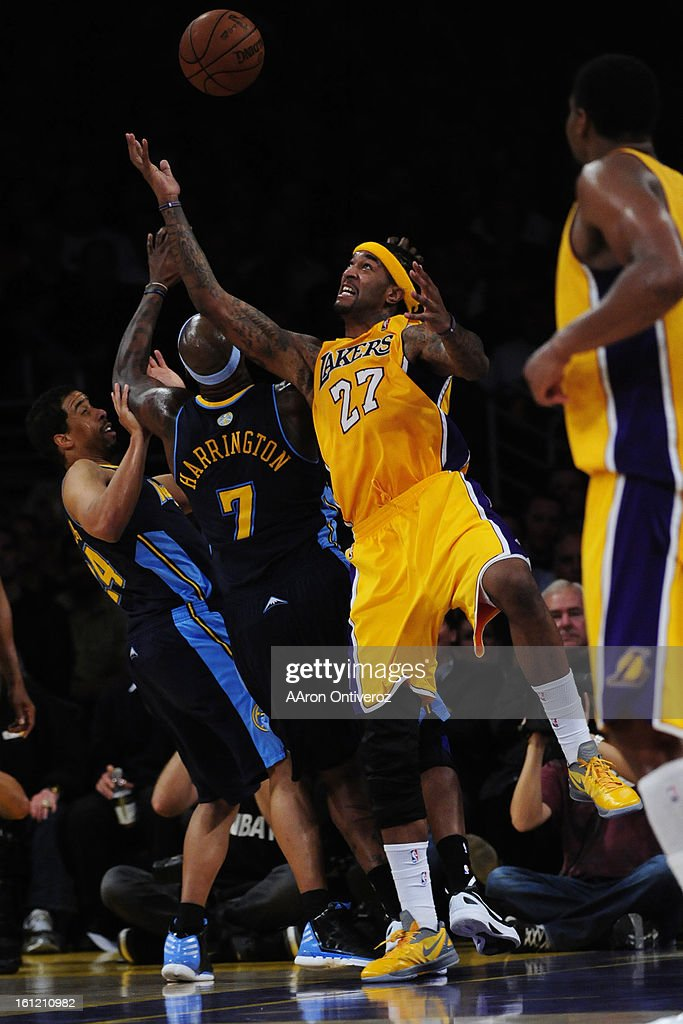 Los Angeles Lakers center Jordan Hill goes for a rebound over Denver Nuggets power forward Al Harrington during the second half of game two of their...
