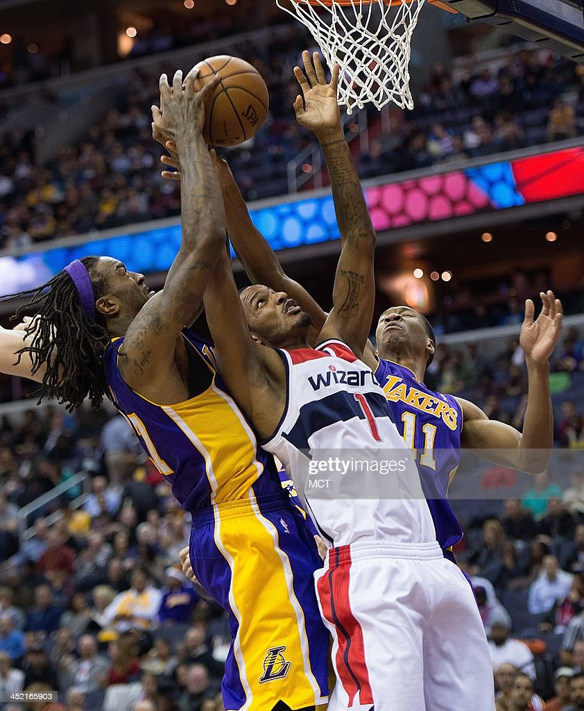 Los Angeles Lakers center Jordan Hill left and shooting guard Wesley Johnson battle for a rebound with Washington Wizards small forward Trevor Ariza...