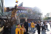 Los Angeles Lakers fans pose for a photo in front of the Earvin 'Magic' Johnson statue outside Staples Center prior to Game One of the Western...
