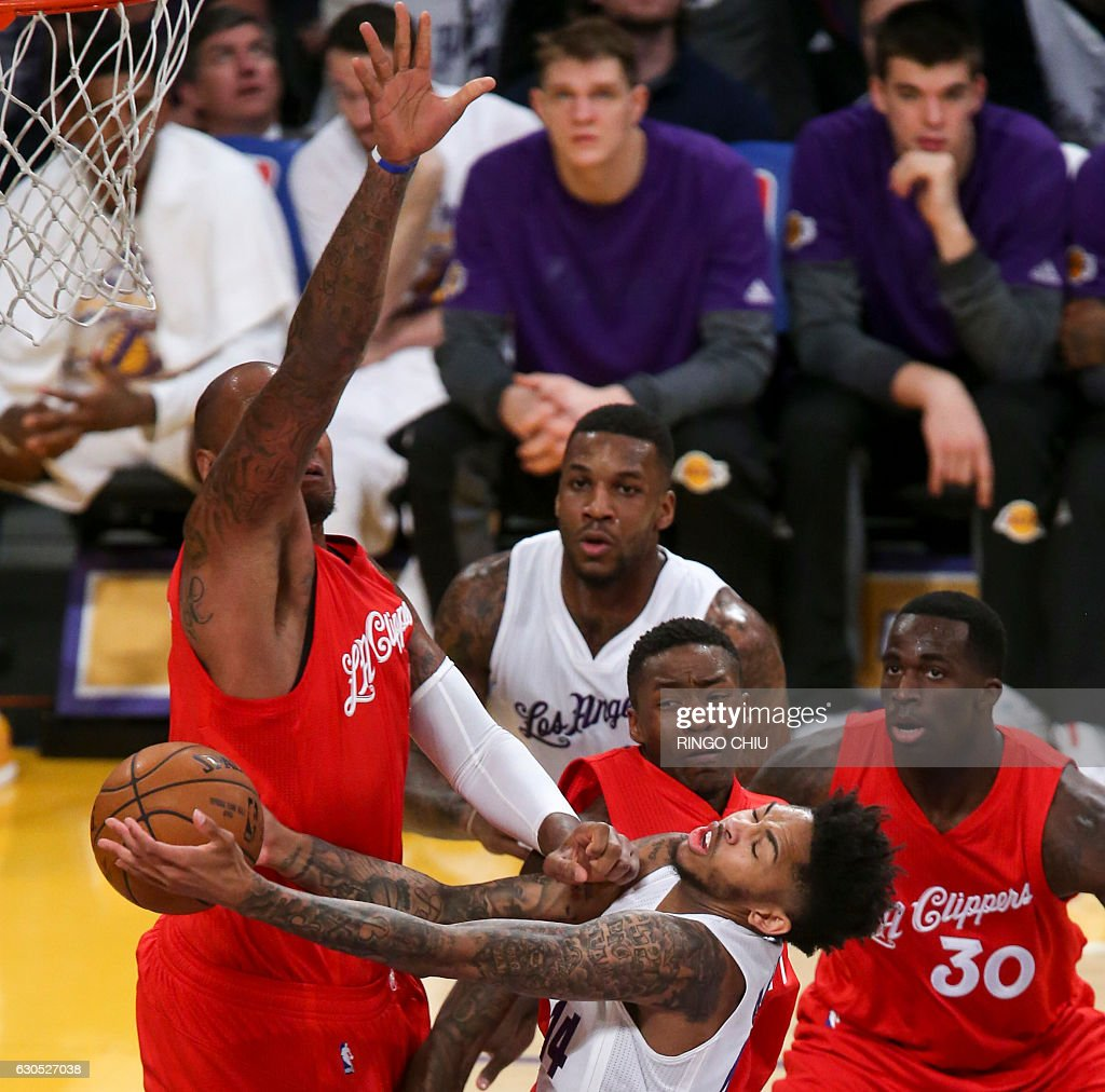 Los Angeles Lakers forward Brandon Ingram (#14)gets fouled by Los Angeles Clippers forward Marries Speights (#5) during their NBA game at Staples Center in Los Angeles, California on December 25, 2016. / AFP / RINGO
