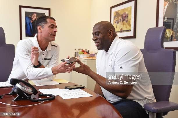 Los Angeles Lakers General Manager Rob Pelinka and President of Basketball Operations Magic Johnson make a phone call in the draft room during the...