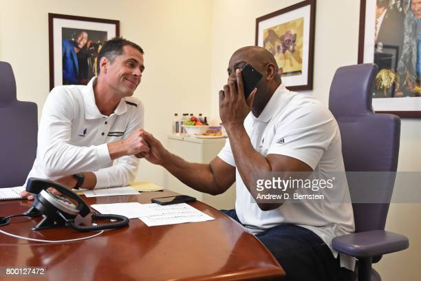 Los Angeles Lakers General Manager Rob Pelinka and President of Basketball Operations Magic Johnson shake hands and make a phone call in the draft...