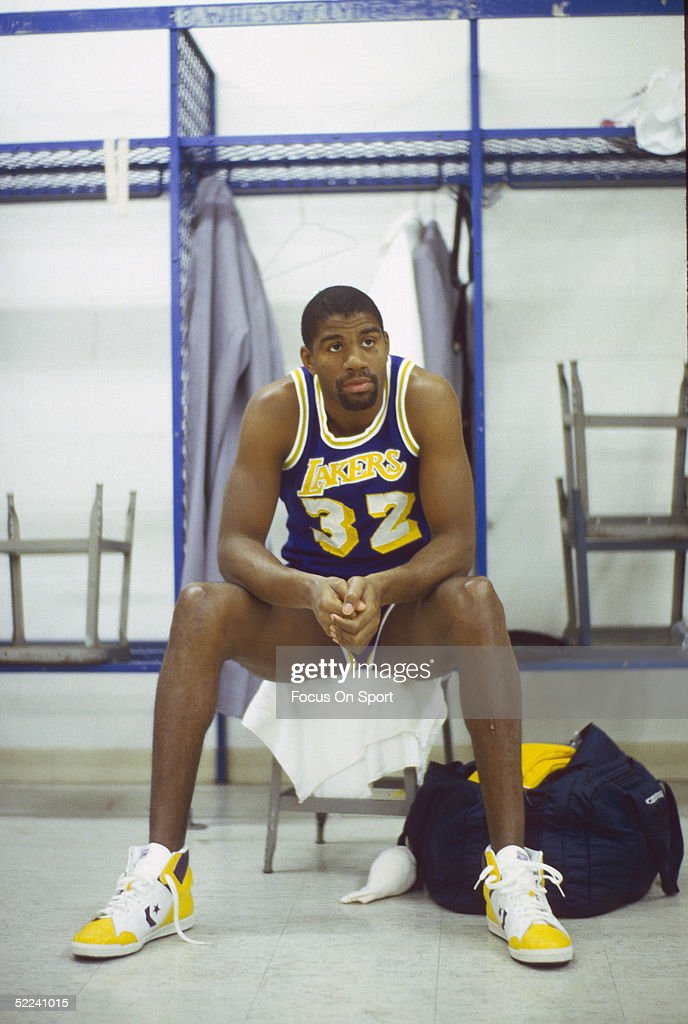 Los Angeles Lakers' guard Earvin 'Magic' Johnson sits in a locker room in a circa 1980s photo