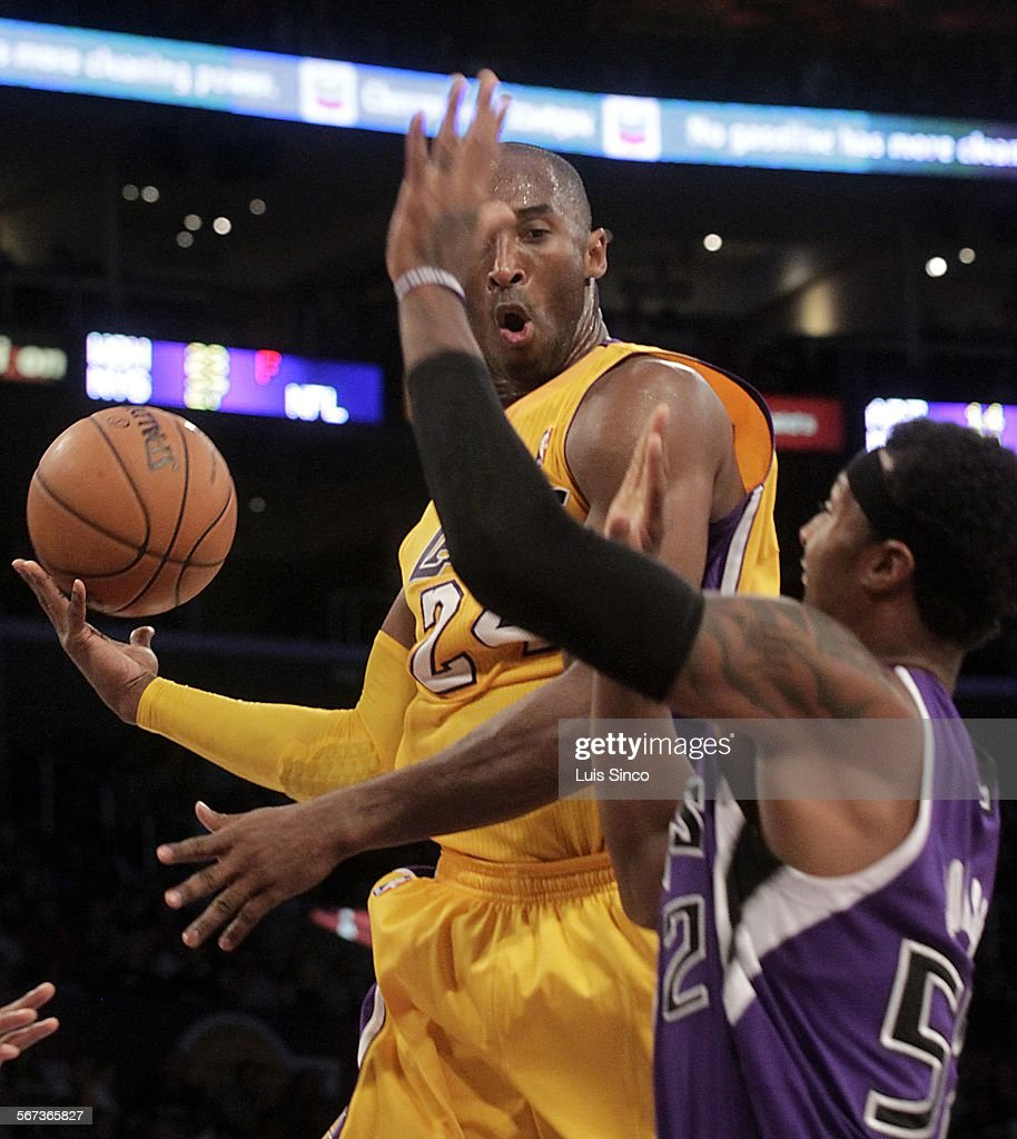 Los Angeles Lakers guard Kobe Bryant dishes off a pass as he drives to the bucket against Sacramento Kings forward James Johnson in the second...