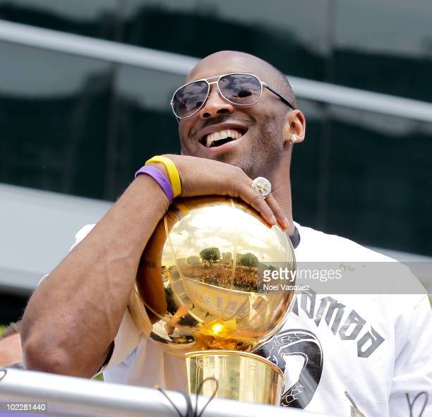 Los Angeles Lakers guard Kobe Bryant laughs with the championship trophy while riding in the victory parade for the the NBA basketball champion team...