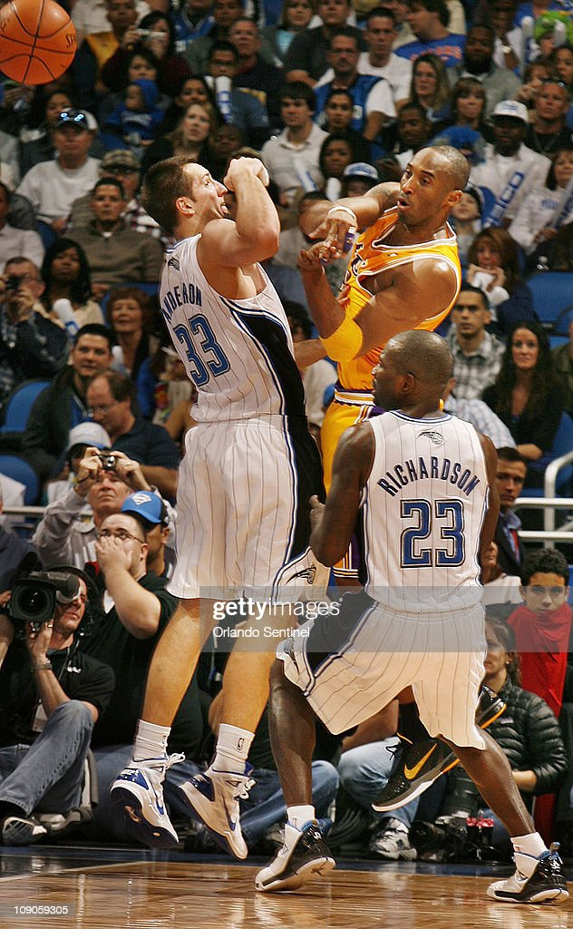 Los Angeles Lakers guard Kobe Bryant passes the ball between Orlando Magic forward Ryan Anderson (33) and Orlando guard Jason Richardson (23) during an NBA game at the Amway Center on Sunday, February 13, 2011, in Orlando, Florida. Orlando won the game 89-75.