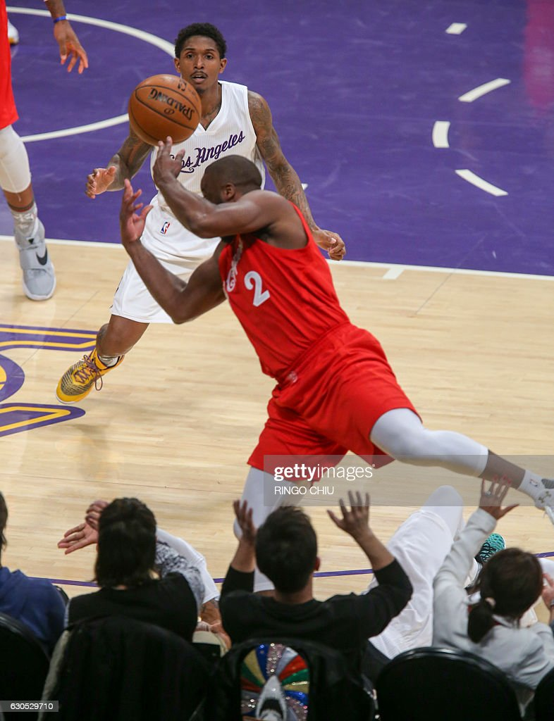 Los Angeles Lakers guard Louis Williams (23) looks on as Los Angeles Clippers guard Raymond Felton (#2) jumps to save a ball during their NBA game at Staples Center in Los Angeles, California on December 25, 2016. The Lakers won 111-102. / AFP / RINGO