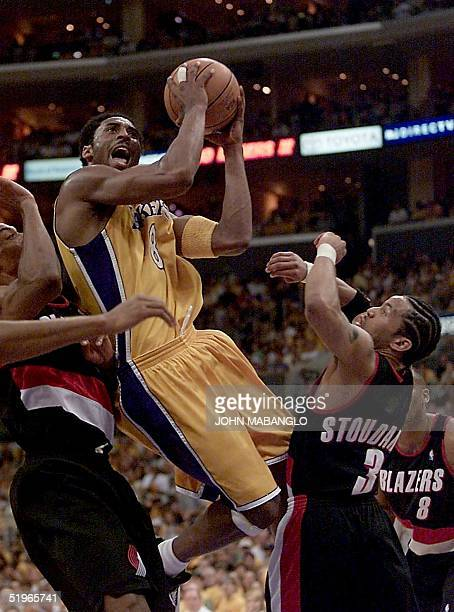 Los Angeles Lakers' Kobe Bryant goes up to score before Portland Trail Blazers' Damon Stoudamire and Blazers Scottie Pippen during the first quarter...