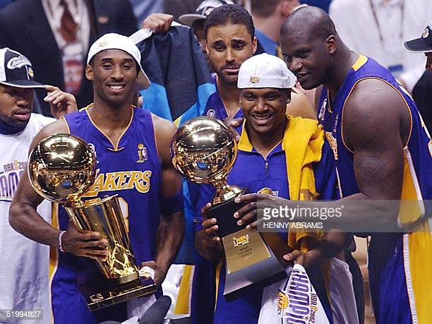 Los Angeles Lakers Kobe Bryant Rick Fox Linsey Hunter and Shaquille O'Neal stand with the championship and MVP trophies after game four of the NBA...