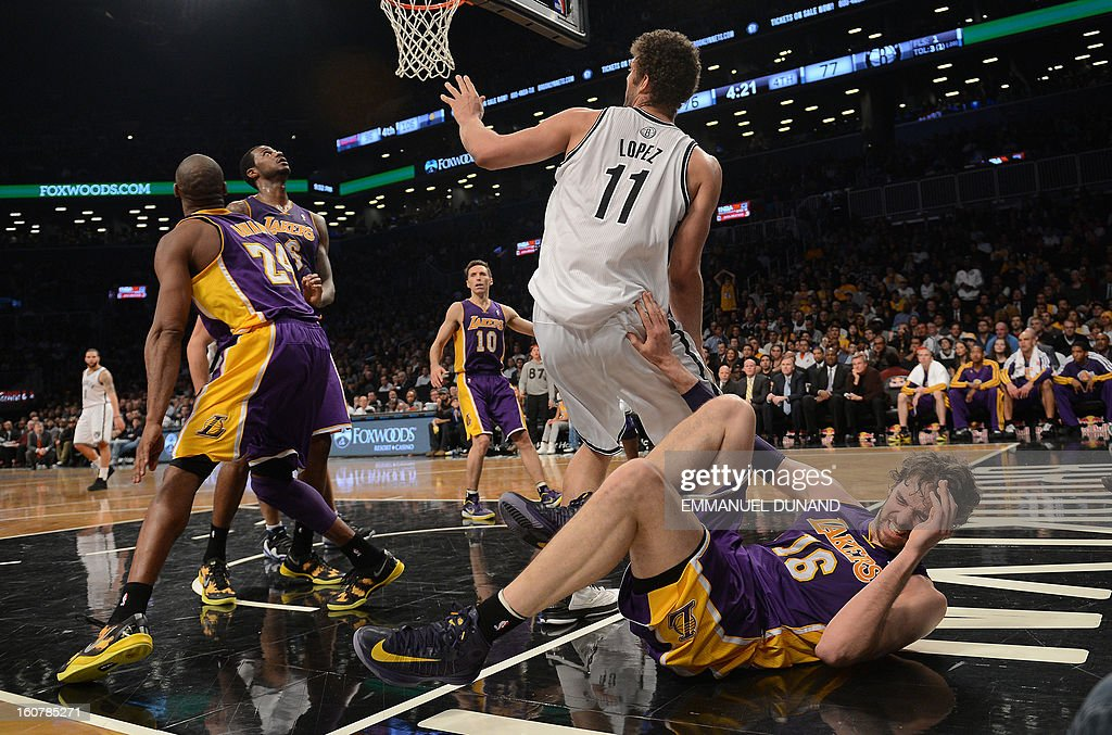 Los Angeles Lakers' Pau Gasol (R) falls after injuring himself against the Brooklyn Nets during their NBA game at the Barclays Center in the Brooklyn borough of New York City, February 5, 2013. AFP PHOTO/Emmanuel Dunand