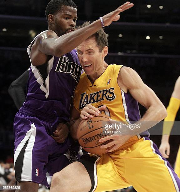 Los Angeles Lakers point guard Steve Nash leans a shoulder into Sacramento Kings defender Aaron Brooks in the first quarter of a preseason NBA game...