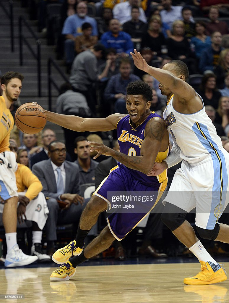 Los Angeles Lakers small forward Nick Young (0) drives the baseline on Denver Nuggets shooting guard Randy Foye (4) during the third quarter November 13, 2013 at Pepsi Center.