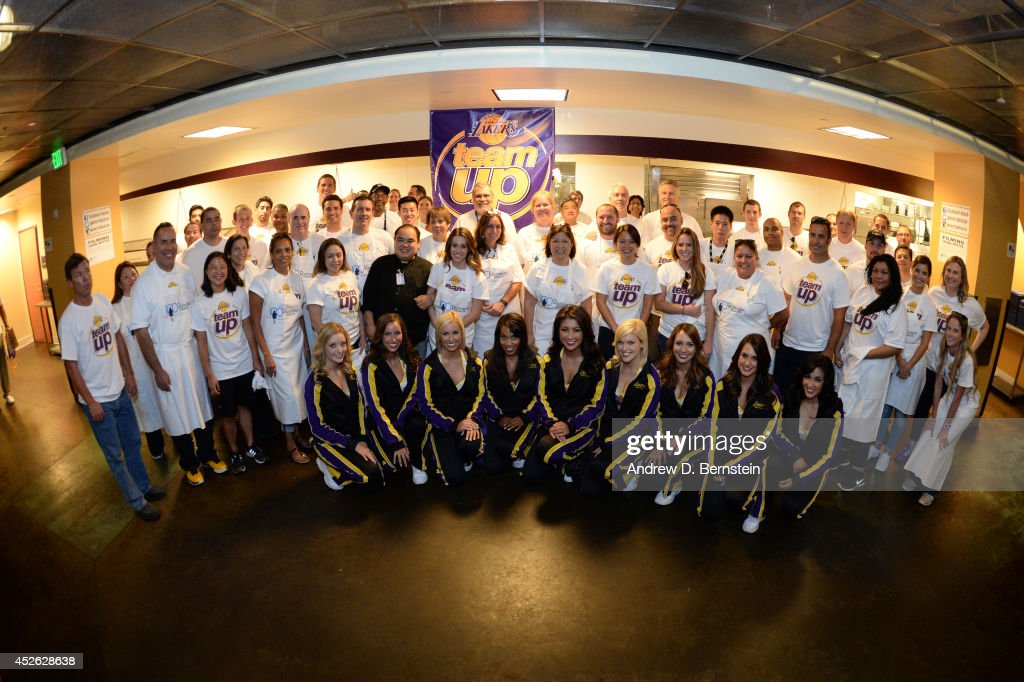 Los Angeles Lakers volunteers and members of the Laker Girls pose for a group photo during a Team Up Event at the Midnight Mission on July 24, 2014 in Los Angeles, California.