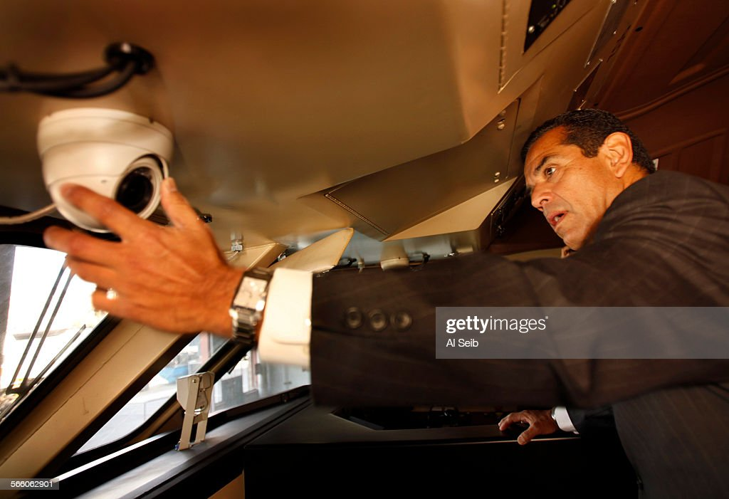 Los Angeles Mayor Antonio Villaraigosa takes a close look at one of the two inward–facing cameras that have been installed in a Metrolink train...