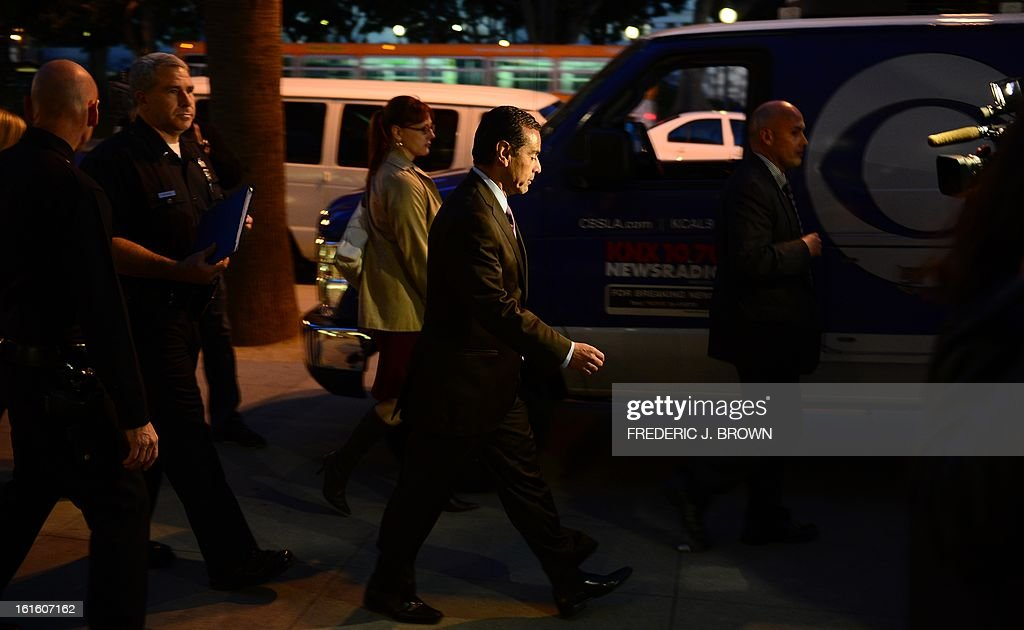 Los Angeles Mayor Antonio Villaraigosa walks in front of police officer addressing the media outside police headquarters in downtown Los Angeles on February 12, 2013 in California, in regards to the case of suspected cop killer Christopher Dorner. The LA Times reported a single gunshot was heard as police moved in on a mountain cabin where Dorner was believed to be barricaded in Big Bear, some 100 miles east of downtown Los Angeles. Meanwhile, a Los Angeles Police Department (LAPD) spokesman was cited as saying the force believed Dorner died inside the burning cabin in the mountains. AFP PHOTO / Frederic J. BROWN