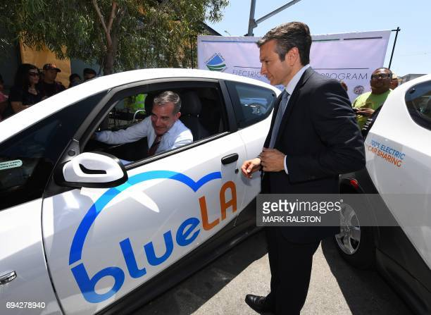 Los Angeles Mayor Eric Garcetti tries out a car beside Serge Amabile from the French company Blue Solutions at the launch of what is being billed as...