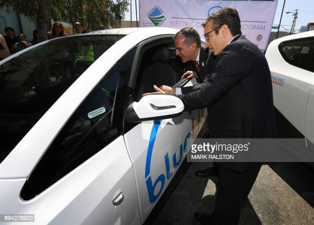 Los Angeles Mayor Eric Garcetti views a car beside Serge Amabile from the French company Blue Solutions at the launch of what is being billed as the...