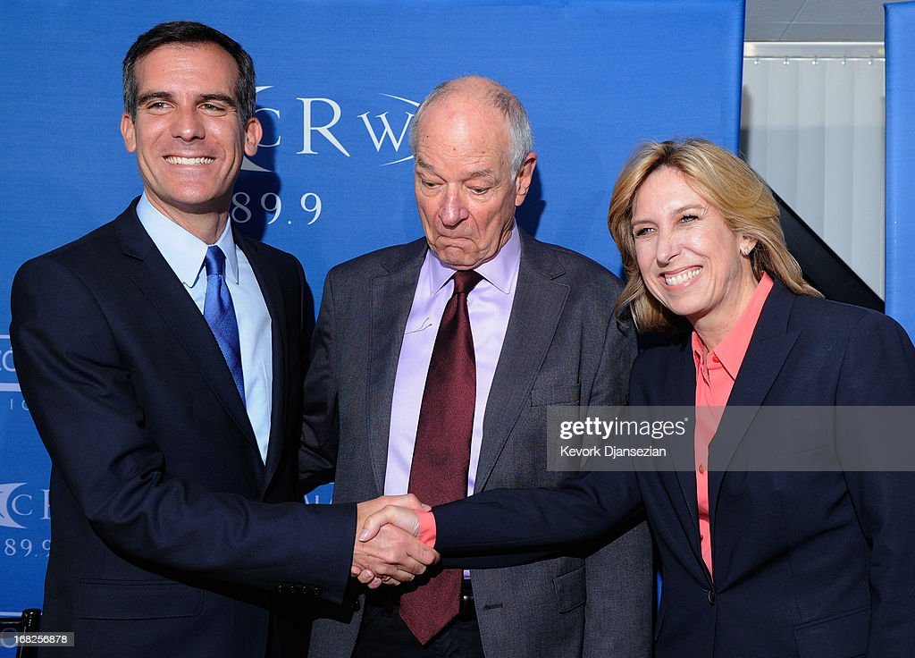 Los Angeles mayoral candidates City Councilman Eric Garcetti (L) and City Controller Wendy Greuel (R) pose for a handshake with moderator Warren Olney, of radio station KCRW, after a debate hosted by Zocalo Public Square and KCRW at the Petersen Automotive Museum on May 7, 2013 in Los Angeles, California. Garcetti and Greuel are preparing for a May 21 runoff vote to determine which will be the next mayor of Los Angeles.