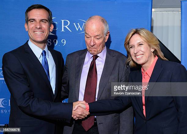 Los Angeles mayoral candidates City Councilman Eric Garcetti and City Controller Wendy Greuel pose for a handshake with moderator Warren Olney of...