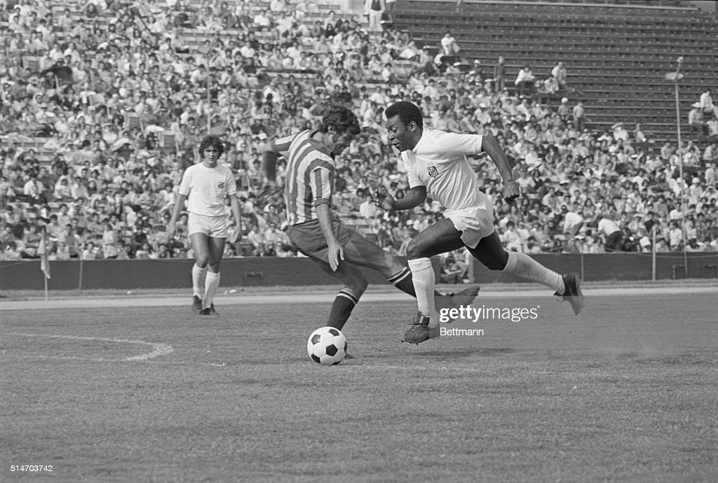 Pele of Brazil's Santos soccer team dribbles the ball down the field of the Coliseum as Guadalajara Mexico defensive player Gustavo Pena tries to...
