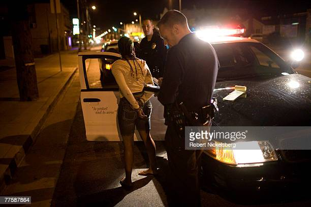 Los Angeles Police Department gang unit officers question a woman stopped for erratic driving September 20 2007 in south central Los Angeles...