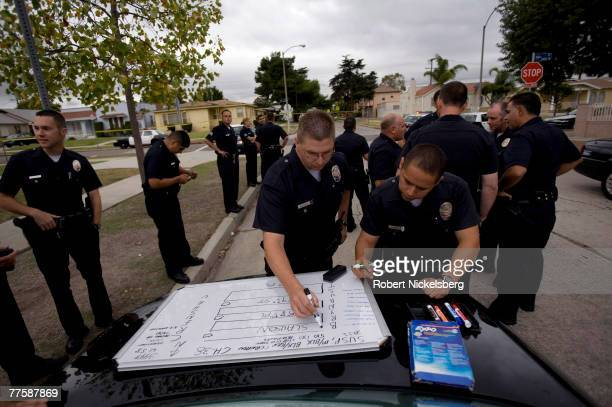 Los Angeles Police Department gang unit officers set up a small command center outside of a Crime Scene Investigation area after a 22year old man...
