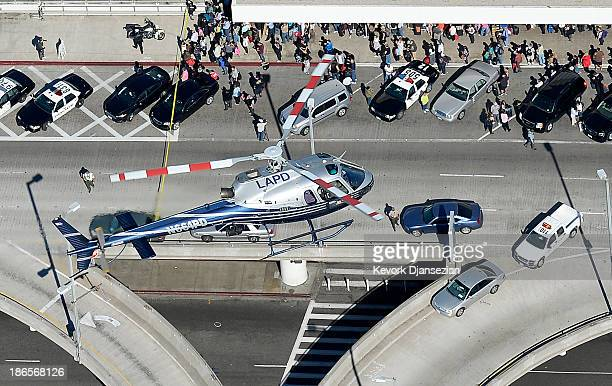 Los Angeles Police Department helicopter flies above a crowd of passengers waiting outside the Los Angeles International Airport after a shooting...
