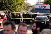 Los Angeles Police Department officers and investigators gather at a command post where a gunman shot and wounded two men in the underground parking...