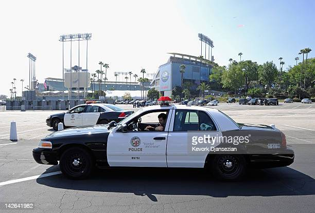 Los Angeles Police Department officers patrol in squad car the parking lot of Dodger Stadium prior to the home opener aginst the Pittsburgh Pirates...
