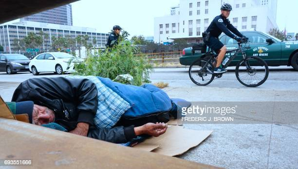 Los Angeles Police Department officers patrol on bicycles past a homeless man napping with cigarette in hand at his encampment on a downtown sidewalk...