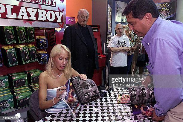 Los Angeles Police Department Patrol Officer Ginger Harrison signs a copy of the July 2001 Playboy Magazine for a fan at a Tower Records store in...