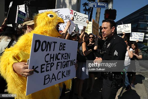 Los Angeles police officer talks with a protester dressed as a chicken during a demonstration against US President Donald Trump outside the office of...