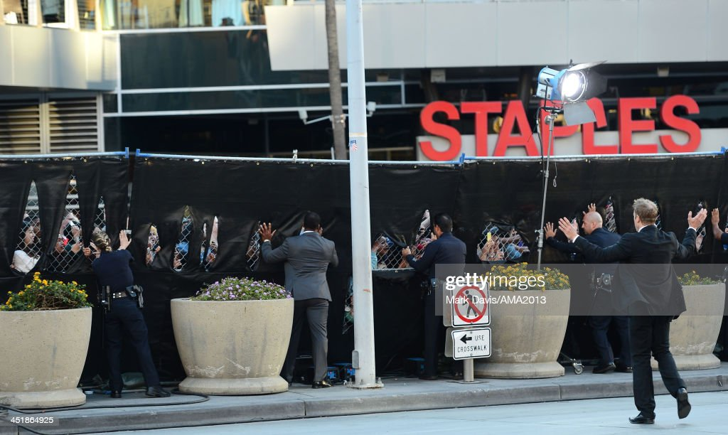 Los Angeles Police officers and security guards reinforce a fence as fans rush to see the arrival of band members from the musical group 'One Direction' at the 2013 American Music Awards at Nokia Theatre L.A. Live on November 24, 2013 in Los Angeles, California.
