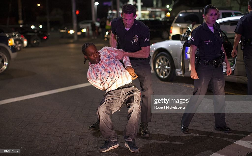 Los Angeles Police officers move a handcuffed man January 30, 2013 after he and another man tried to outrun the police after a LAPD patrol car attempted to pull the suspects over in downtown Los Angeles, California. Both men were arrested. The car's driver was charged with evading the police while in pursuit and the passenger was found with an outstanding arrest warrant on him.