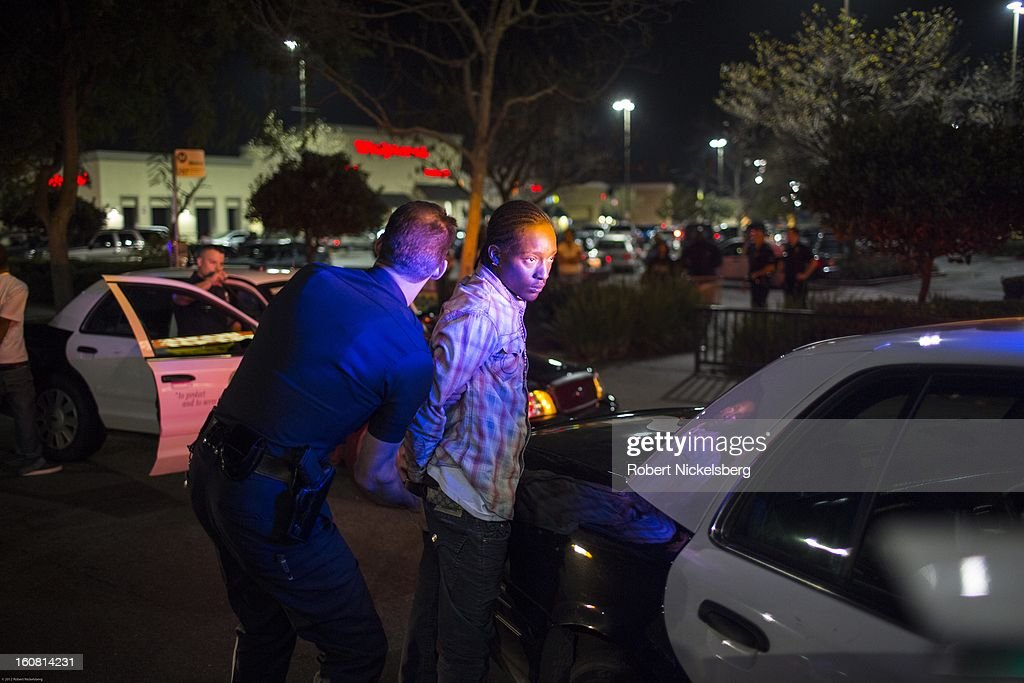 Los Angeles Police officers move a handcuffed man to a patrol car January 30, 2013 after he and another man, far left, tried to outrun the police after a LAPD patrol car attempted to pull the suspects over in downtown Los Angeles, California. Both men were arrested. The car's driver was charged with evading the police while in pursuit and the passenger was found with an outstanding arrest warrant on him.