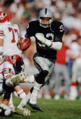 Los Angeles Raiders running back Marcus Allen dodges a tackle as he runs with the ball during a 1986 NFL game against the Atlanta Falcons at the Los...