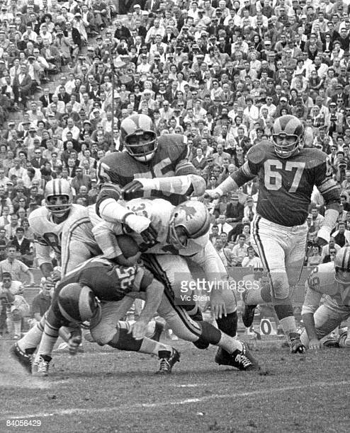 Los Angeles Rams Hall of Fame defensive end Deacon Jones trailed by defensive tackle Urban Henry wraps up Detroit Lions fullback Nick Pietrosante...