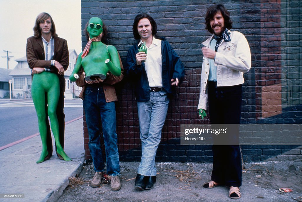 Los Angeles rock band The Doors stand alongside a brick building holding sections of a green mannequin. Left to right are: Ray Manzarek, keyboards; Robbie Krieger, guitar; Jim Morrison, vocals; John Densmore, drums.