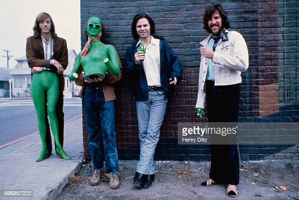 Los Angeles rock band The Doors stand alongside a brick building holding sections of a green mannequin Left to right are Ray Manzarek keyboards...