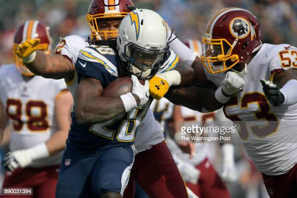 Los Angeles running back Melvin Gordon center is brought down by Washington outside linebacker Ryan Anderson left and Washington inside linebacker...
