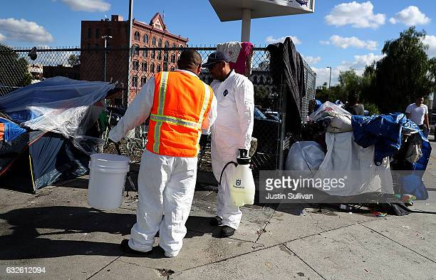 Los Angeles sanitation workers prepare to clean the area near a homeless encampment on January 24 2017 in Los Angeles California According to a 2016...