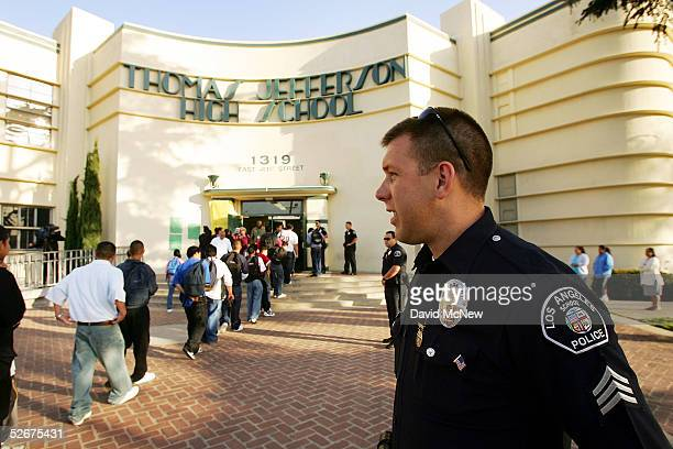Los Angeles School Police Sgt Robert Carlborn watches over students lining up to pass through a security check point in the aftermath of two apparent...