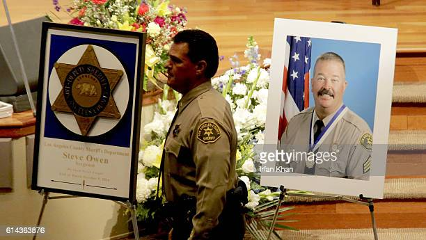 Los Angeles Sheriff's deputy passes by a portrait of slain Los Angeles County Sheriff's Sgt Steve Owen prior to his funeral service at Lancaster...